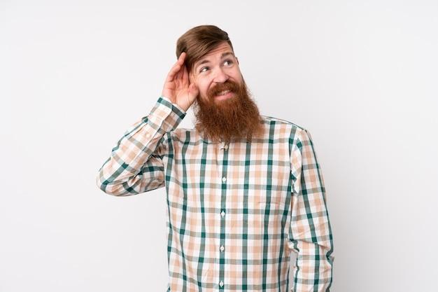 Roodharige man met lange baard over witte muur twijfels en met verwarde gezichtsuitdrukking