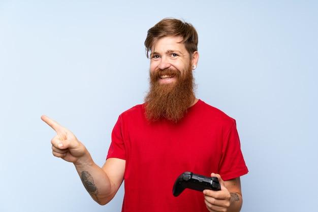 Roodharige man met lange baard spelen met een videogame controller verrast en wijzende vinger naar de kant