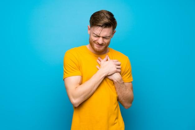 Roodharige man over blauwe muur met een pijn in het hart