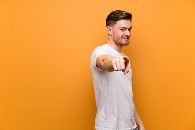 Roodharige man over bruine muur wijst vinger naar je met een zelfverzekerde uitdrukking