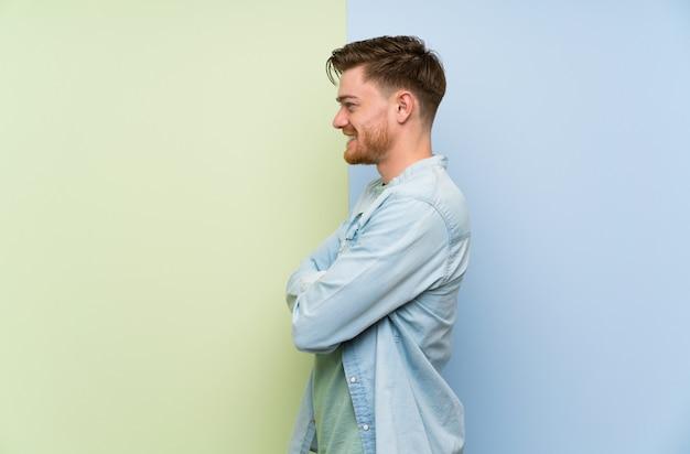 Roodharige man over kleurrijke muur in zijpositie