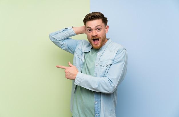 Roodharige man over kleurrijke muur verrast en wijzende vinger naar de kant