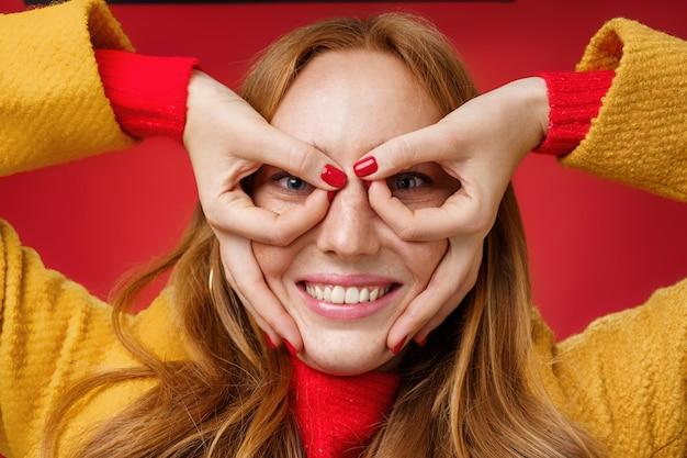 Roodharige meid houdt van gek doen en doen alsof ze weer een kind is en een grappig masker maakt met vingers op het gezicht als een superheld die breed glimlacht, speels rond de rode achtergrond.