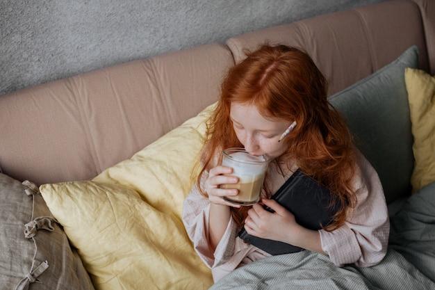 Roodharige meisje drinkt koffie in bed en legt haar notitieboekje opzij.