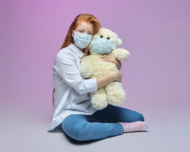 Roodharige meisje en een teddybeer in medische maskers het concept van preventiecovid
