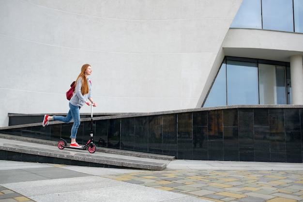 Roodharige meisje gekleed in grijze hoody, blauwe spijkerbroek en rode sneakers rijden kick scooter in de buurt van modern gebouw