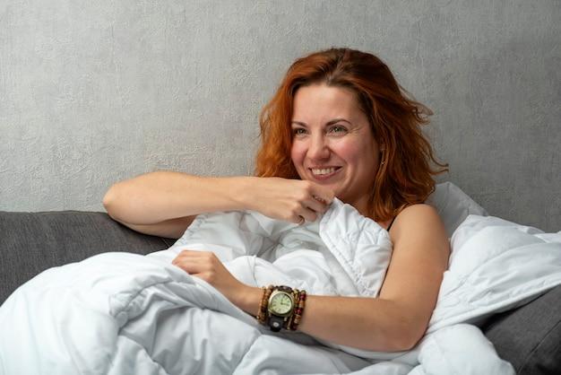 Roodharige meisje glimlacht en bedekt met een witte deken