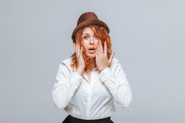 Roodharige meisje in bruine hoed en wit overhemd verrast
