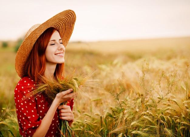 Roodharige meisje in een rode jurk aan het tarweveld