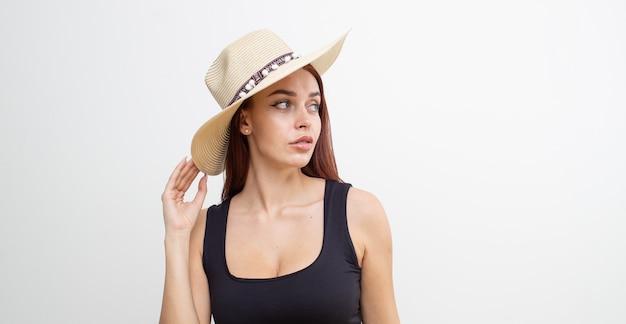 Roodharige meisje in een zwart t-shirt en strooien hoed poseren op een witte achtergrond