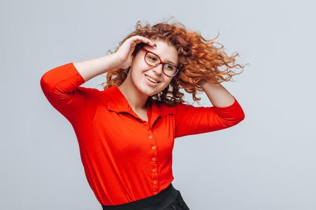Roodharige meisje in glazen en rode blouse poseren in de wind
