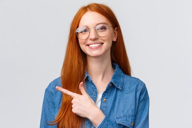 Roodharige meisje in glazen wijzende vinger naar links en aangenaam glimlachen