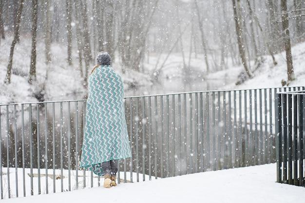 Roodharige meisje in grijze hoed, bedekt met blauwe patronen plaid genieten van sneeuwval staande achterkant op de brug in de buurt van de rivier