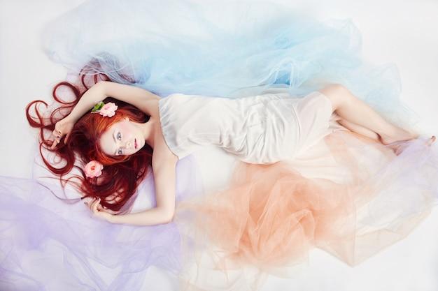 Roodharige meisje in lichte luchtige gekleurde jurk leugens