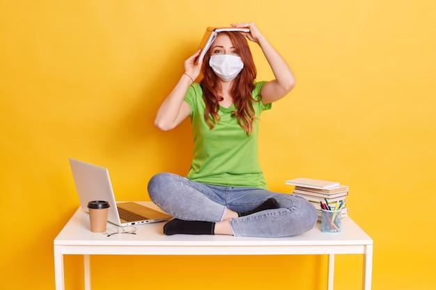 Roodharige meisje in medische masker zit met gekruiste benen op tafel, spijkerbroek en groen t-shirt dragen, moe van lang ons afstandsonderwijs