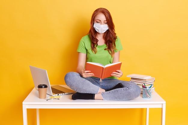 Roodharige meisje in medische masker zit op tafel met computer en boeken, lezen, kijkt geconcentreerd