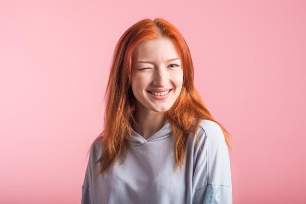 Roodharige meisje knipoogt in studio op roze achtergrond