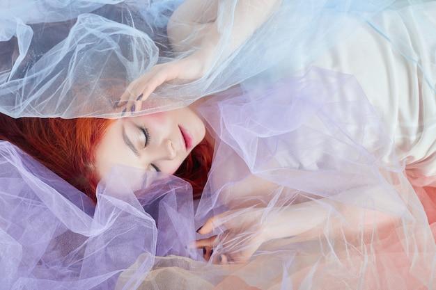 Roodharige meisje lichte lucht gekleurde jurk ligt op de vloer