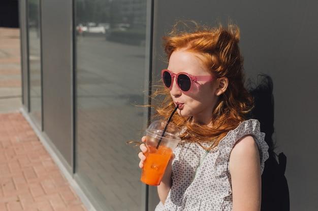 Roodharige meisje limonade drinken uit een plastic glas.