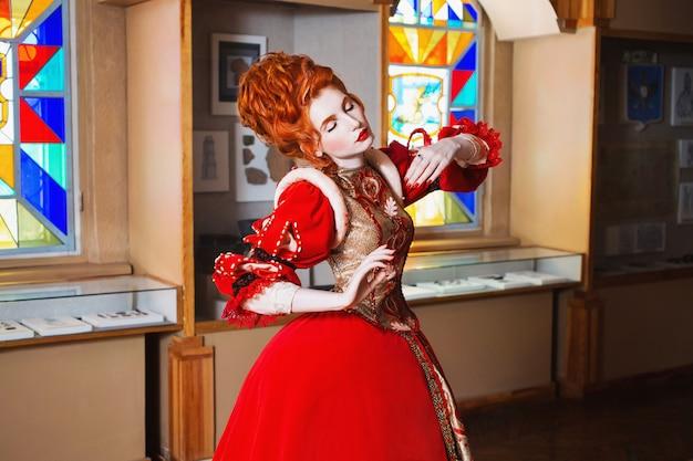 Roodharige meisje met blauwe ogen in een rode jurk. koningin met een hoog kapsel. vintage afbeelding. een vrouw met een bleke huid