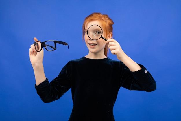 Roodharige meisje met bril voor zicht en een vergrootglas op een blauwe achtergrond.