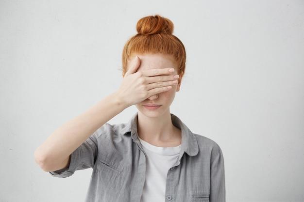 Roodharige meisje met haarbroodje ogen onder de hand verbergen terwijl ze zich schaamde. ernstige jonge vrouw in oorzakelijke kleding die gezicht bedekt met hand. menselijke gezichtsuitdrukkingen en emoties