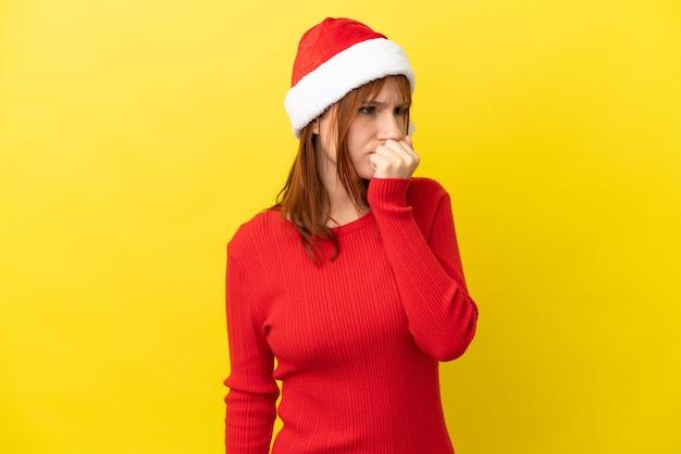 Roodharige meisje met kerstmuts geïsoleerd op gele achtergrond twijfels