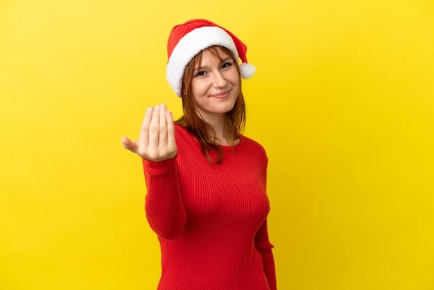 Roodharige meisje met kerstmuts geïsoleerd op gele achtergrond uitnodigend om met de hand te komen. blij dat je gekomen bent