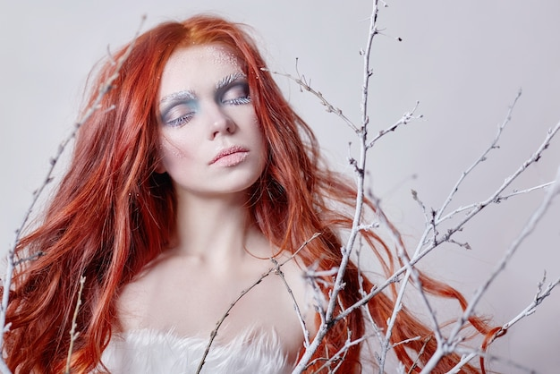 Roodharige meisje met lang haar, een gezicht bedekt met sneeuw met rijp. witte wenkbrauwen en wimpers bij vorst, een boomtak bedekt met sneeuw. sneeuwkoningin en winter. winter make-up vrouw gezicht, rood hoofd