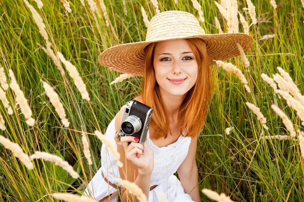 Roodharige meisje met oude camera in de weide.