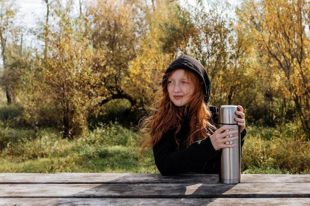 Roodharige meisje op een herfstpicknick gaat thee drinken