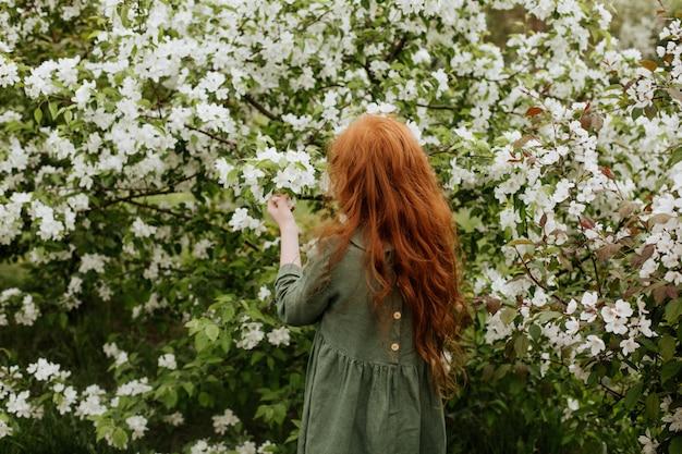 Roodharige meisje staat onder bloeiende takken van een appelboom op een zonnige lentedag.