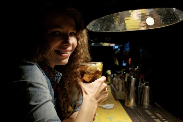 Roodharige meisje zitten in de bar (pub) ijzige cocktail drinken en glimlachen