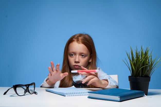 Roodharige meisje zittend aan een tafel met schoolboeken lessen schoolopleiding. hoge kwaliteit foto
