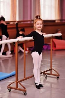 Roodharige meisjesballerina die dichtbij de choreografische machine glimlacht