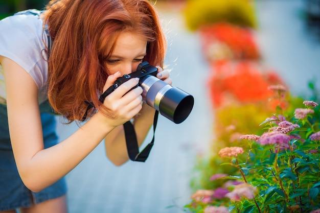 Roodharige meisjesfotograaf die foto's van bloemen maakt