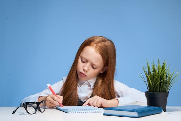 Roodharige meisjeszitting bij een lijst met de schoolkinderjaren van het leerboekenonderwijs