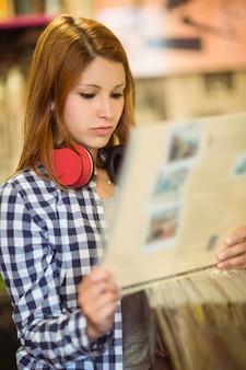 Roodharige met check-shirt met een vinyl
