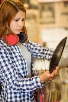 Roodharige met een koptelefoon rond de nek met een vinyl