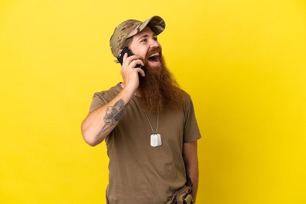 Roodharige militaire man met dog tag geïsoleerd op gele achtergrond die een gesprek voert met de mobiele telefoon