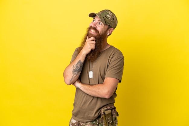 Roodharige militaire man met dog tag geïsoleerd op gele achtergrond op zoek naar de kant