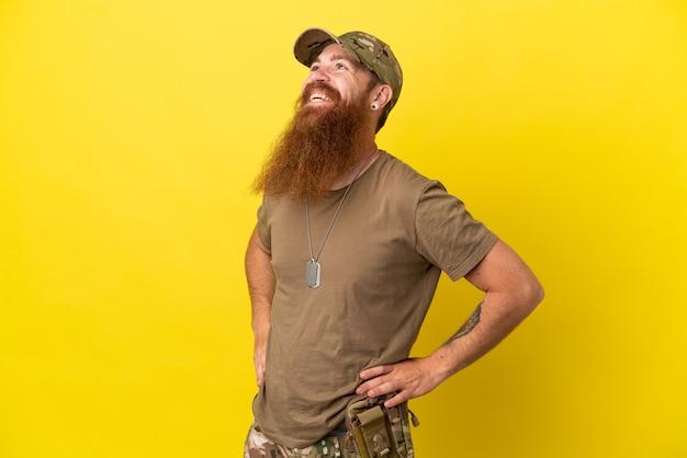 Roodharige militaire man met dog tag geïsoleerd op gele achtergrond poseren met armen op heup en lachend