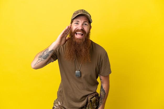 Roodharige militaire man met dog tag geïsoleerd op gele achtergrond schreeuwen met mond wijd open