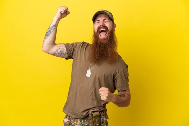 Roodharige militaire man met dog tag geïsoleerd op gele achtergrond vieren een overwinning