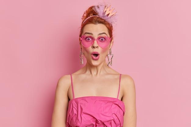 Roodharige modieuze vrouw staart verrassend houdt mond open reageert op geweldig nieuws draagt trendy zonnebril en jurk geïsoleerd over roze muur. stijlconcept