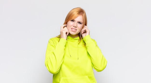 Roodharige mooie vrouw die boos, gestrest en geïrriteerd kijkt, beide oren bedekt met een oorverdovend geluid, geluid of luide muziek