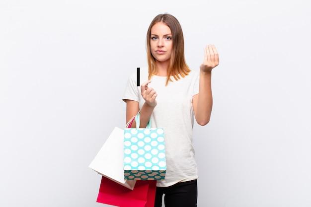 Roodharige mooie vrouw die capice of geldgebaar maakt en zegt dat je je schulden moet betalen! met boodschappentassen
