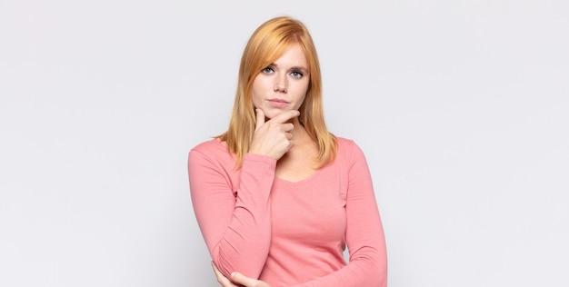 Roodharige mooie vrouw die ernstig, verward, onzeker en attent kijkt, twijfelt tussen opties of keuzes