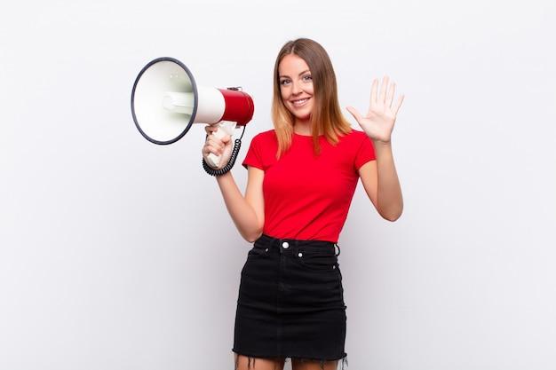 Roodharige mooie vrouw die vriendelijk glimlacht en kijkt, nummer vijf of vijfde met vooruit hand toont, aftellend met een megafoon