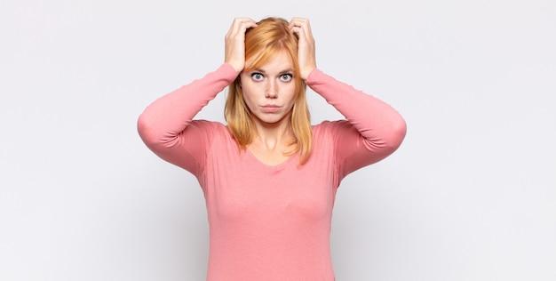 Roodharige mooie vrouw die zich gefrustreerd en geïrriteerd voelt, ziek en moe van mislukking, beu met saaie, saaie taken